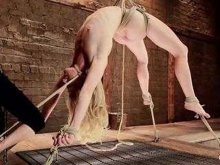 Don't you just love seeing a blondie getting roughly treated and punished? This one just reached her limitations as she hangs there while being tied on the floor. It's a good thing she's slim 'coz she's flexible. The mistress starts rubbing her pussy with a vibrator and fingers her muff so hard that it turns red!