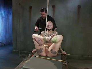 Punk slut Sparky thought she as a bad girl, shaving her head and covering that sexy body with tattoos. Well know, this guy shows her what bad is all about and ties her young body before performing a punishment. He spanks her feet and haunches with a stick and to really teach her a lesson, the guy rubs her pussy likewise