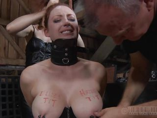 Horny redhead Holly is all tied up with a big collar around her neck. The two guys demanded one boob for each one of 'em and sticked metal clamps on her nipples, after writing their names on her tits. They tie her up and make her stand on her tip-toes. She looks so hot and provocative. Don`t you think so?