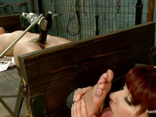 Hot redhead female-dominator with the assist of her boy is punishing this cutie. This babe licks the chick's feet while a fake penis rubs her cookie and then uses another bondage device, this time to keep these legs up. With a small electric wand she socks these feet and the fellow bonks the sex slave's mouth.