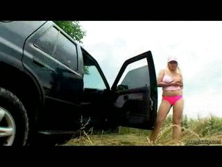 A blond teenage girl with very large tits is standing next to a car. She lifts one of her tits out of her T-shirt and plays with it, doing the same with one as well as the other of them later on. When she is stripped she gets into the car and uses a dildo