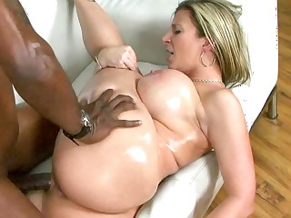 A hot milf with large tits is getting a fat black dick in her mouth