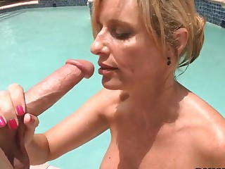 Busty tow-haired milf Jodi West sucks a heavy dick hard by someone's skin pool