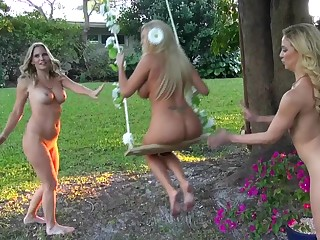 Three girls are bringing off around naked in the garden in a threesome