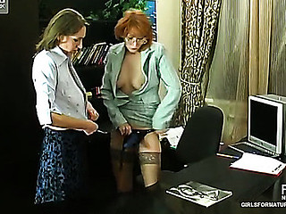Aged receptionist forcing her younger co-worker into naughty strap-on play