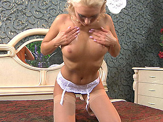 Dazzling blondie attaches her barely patent nylons to her white garter
